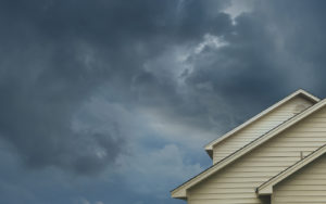 Dark clouds behind a nondescript two story home.