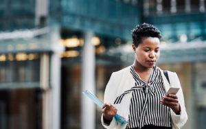 Female entrepreneur carrying files and reading email on her phone.